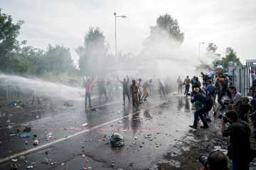 Hungarian police use water cannons on migrants at the Horgos 2 border crossing between Serbia and Hungary, Sept. 16, 2015. (EPA/Tamas Soki)