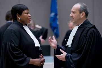 Emmanuel Altit, right, defense lawyer for former Ivory Coast president Laurent Gbagbo talks to prosecutor Fatou Bensouda as they wait for the start of his trial at the International Criminal Court in The Hague, Netherlands, Jan. 28, 2016. Gbagbo is in court along with a former youth minister Charles Ble Goude on charges of involvement in violence after 2010 presidential elections that left 3,000 people dead in Ivory Coast, once a haven of stability in West Africa. (AP Photo/Peter Dejong, Pool)