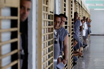 Prisoners look at military guards after returning to their cells at the Combinado del Este prison during a media tour in Havana, Cuba,, April 9, 2013.  (AP Photo/Franklin Reyes)