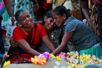 In this Monday, May 18, 2015 photo, Sri Lankan ethnic Tamil women cry at the grave of their relatives who died in a fierce fighting between the army and Tamil Tiger rebels, outside a church in Mullivaikkal, about 335 kilometers (208 miles) northeast of Sri Lanka. Sri Lanka's ethnic Tamil politicians and a few civilians gathered Monday under heavy surveillance at a ceremony to honor thousands of dead on the battleground of the final days of the decades-long civil war that ended in 2009. (AP Photo/Eranga Jayawardena)