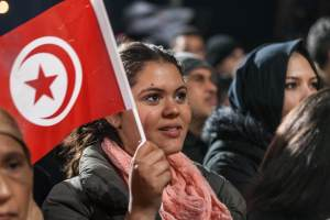 A supporter holds a Tunisian flag as Tunisian presidential candidate Moncef Marzouki gives a speech, after the second round of the country's presidential election, in Tunis,  Dec. 21, 2014. (AP Photo/Ilyess Osmane)