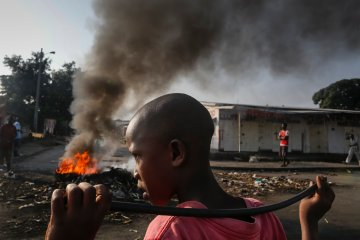 A Burundian boy looks on as he holds a stick in front of a burning barricade during an anti-government demonstration against President Pierre Nkurunziza's bid for a third term in Cibitoke neighborhood of Bujumbura, Burundi, May 29, 2015. EPA/Dai Kurokawa