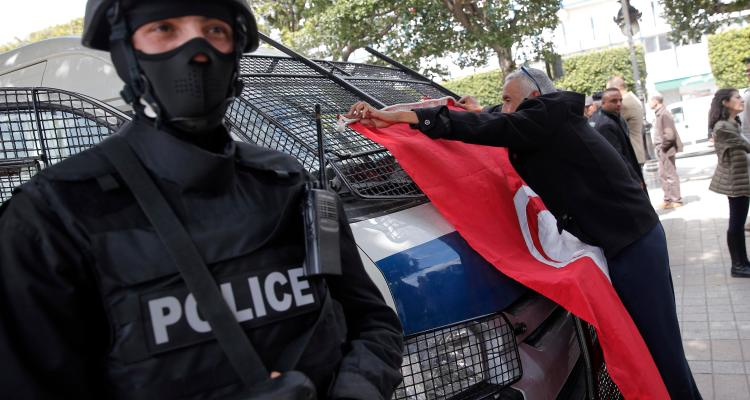 A man places a Tunisian flag onto a police car as a policeman stands guard during a demonstration two days after gunmen attacked the museum and killed scores of people in Tunis, Tunisia, March 20, 2015.  (AP Photo/Christophe Ena, File)