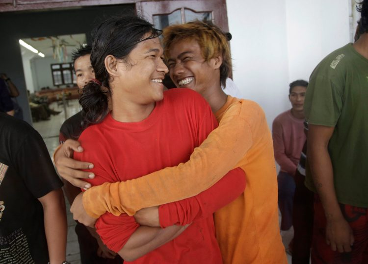 Burmese fishermen hug each other as they wait for their departure to leave the compound of Pusaka Benjina Resources fishing company in Benjina, Indonesia, April 3, 2015. (AP Photo/Dita Alangkara)