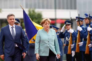 German Chancellor Angela Merkel accompanied by Bosnian Prime Minister Denis Zvizdic, left, arrives at Bosnian Parliament  in Sarajevo, Bosnia, July 9, 2015. (AP Photo/Amel Emric)