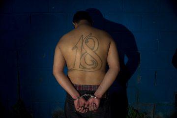 Cesar Vladimir Montoya Climaco, a member of El Salvador's Barrio 18 gagn, stands in front of a wall, handcuffed,  after his arrest in San Salvador, July 28, 2015. (AP Photo/Salvador Melendez)