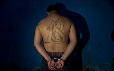 Cesar Vladimir Montoya Climaco, a member of El Salvador's Barrio 18 gagn, stands in front of a wall, handcuffed,  after his arrest in San Salvador, July 28, 2015. (AP Photo/Salvador Melendez)