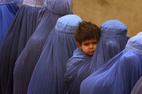Afghan women wearing burqa line up to vote at a polling station in Kabul on , Oct. 9. 2004.   (AP Photo/Emilio Morenatti)