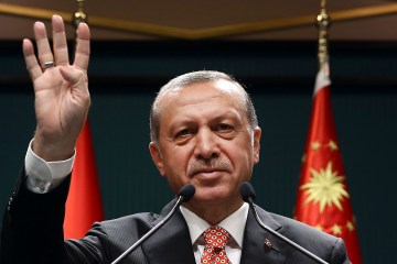 Turkey's President Recep Tayyip Erdogan, waves following a televised address at the presidential palace in Ankara, Turkey,  July 24, 2016. Erdogan has sharply criticised concerns that the large-scale purges, which have left at least thousands of people in jail and about 50,000 fired or suspended, could jeopardise basic freedoms. Press Presidency Press Service via AP, Pool)