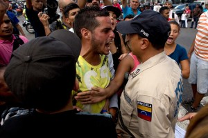 A man waiting in line at a grocery store argues with a Bolivarian National Police officer as he and others wait for food to arrive to the store in Caracas, Venezuela, June 8, 2016.  (AP Photo/Fernando Llano)
