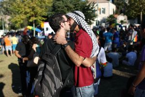 A gay couple including a man wearing an Arab Keffiyeh kiss during the annual Gay Pride parade in Jerusalem, Israel, Aug. 1, 2013.  (EPA/Abir Sultan)