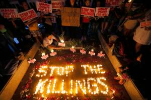 "Human rights activists light candles for the victims of extra-judicial killings around the country in the wake of ""War on Drugs"" campaign by Philippine President Rodrigo Duterte in suburban Quezon city northeast of Manila, Philippines,  Aug. 15, 2016. (AP Photo/Bullit Marquez, File)"