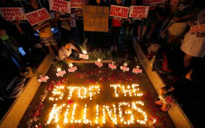 """Human rights activists light candles for the victims of extra-judicial killings around the country in the wake of """"War on Drugs"""" campaign by Philippine President Rodrigo Duterte in suburban Quezon city northeast of Manila, Philippines,  Aug. 15, 2016. (AP Photo/Bullit Marquez, File)"""