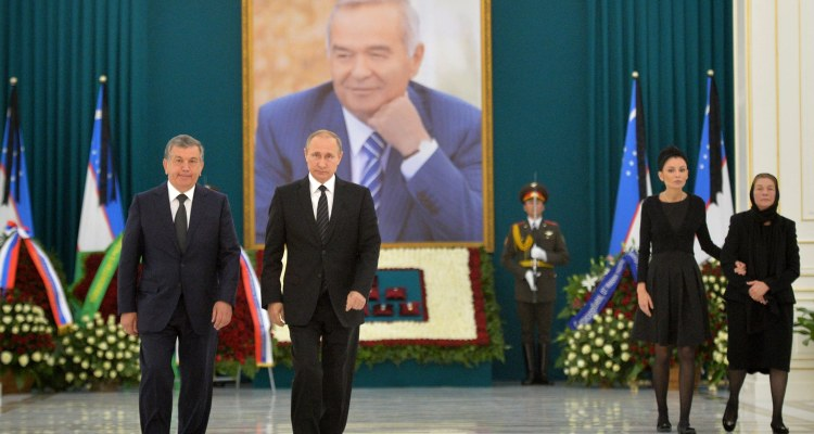 Uzbekistan's Prime Minister Shavkat Mirziyayev, left, and  Russian President Vladimir Putin, walk in front of a portrait of former Uzbek President Islam Karimov, as  Karimov's daughter Lola Karimova-Tillyaeva and widow Tatyana Karomova walk at a cemetery in Samarkand, Uzbekistan, Sept. 6, 2016. (Alexei Druzhinin/Sputnik, Kremlin Pool Photo via AP)