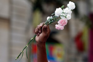 A man holds flowers during a peace march in Bogota, Colombia,  Oct. 12, 2016. Thousands of rural farmers, indigenous activists and students marched in cities across Colombia to demand a peace deal between the government an leftist rebels not be scuttled. (AP Photo/Fernando Vergara)