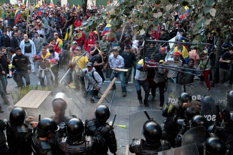 Protesters clash with police in Quito, Ecuador, Aug. 13, 2015. A strike by a broad coalition upset with President Rafael Correa virtually paralyzed the capital, provincial cities and stretches of the Panamerican highway. (AP Photo/Franklin Jacome)