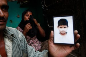 Pannalal, a 33-year-old construction worker in India, holds a photo of his missing eight-year-old daughter while his wife Sheela weeps. (Mansi Thapliyal/Reuters)