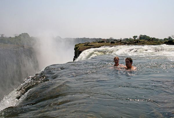 Swimming at the edge of the falls in a naturally formed safe pool, accessed via Livingstone Island. Photo by Ian Restall.
