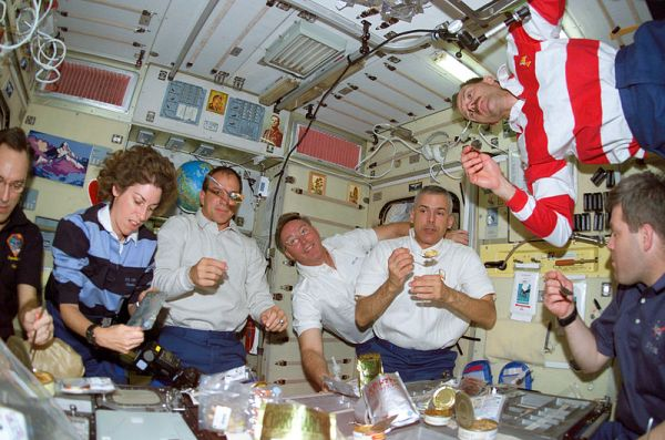 The Expedition Four and STS-110 crewmembers share a meal in the Zvezda Service Module on the International Space Station (ISS). Photo by NASA.