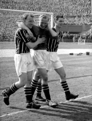 Bert Trautmann is escorted to the touchline by his Manchester City teammates after injuring himself in the line of duty during the 1956 FA Cup Final against Birmingham City at Wembley (Source: www.whoateallthepies.tv)