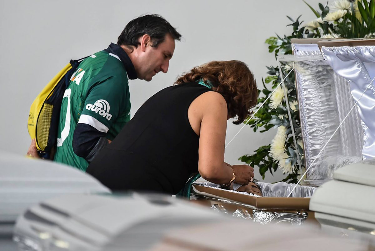 Relatives of Nilson Junior Folle, one of the Brazilian team Chapecoense Real players killed in the plane crash, embrace each other close to the coffin (Photo: AFP/Getty Mirror)
