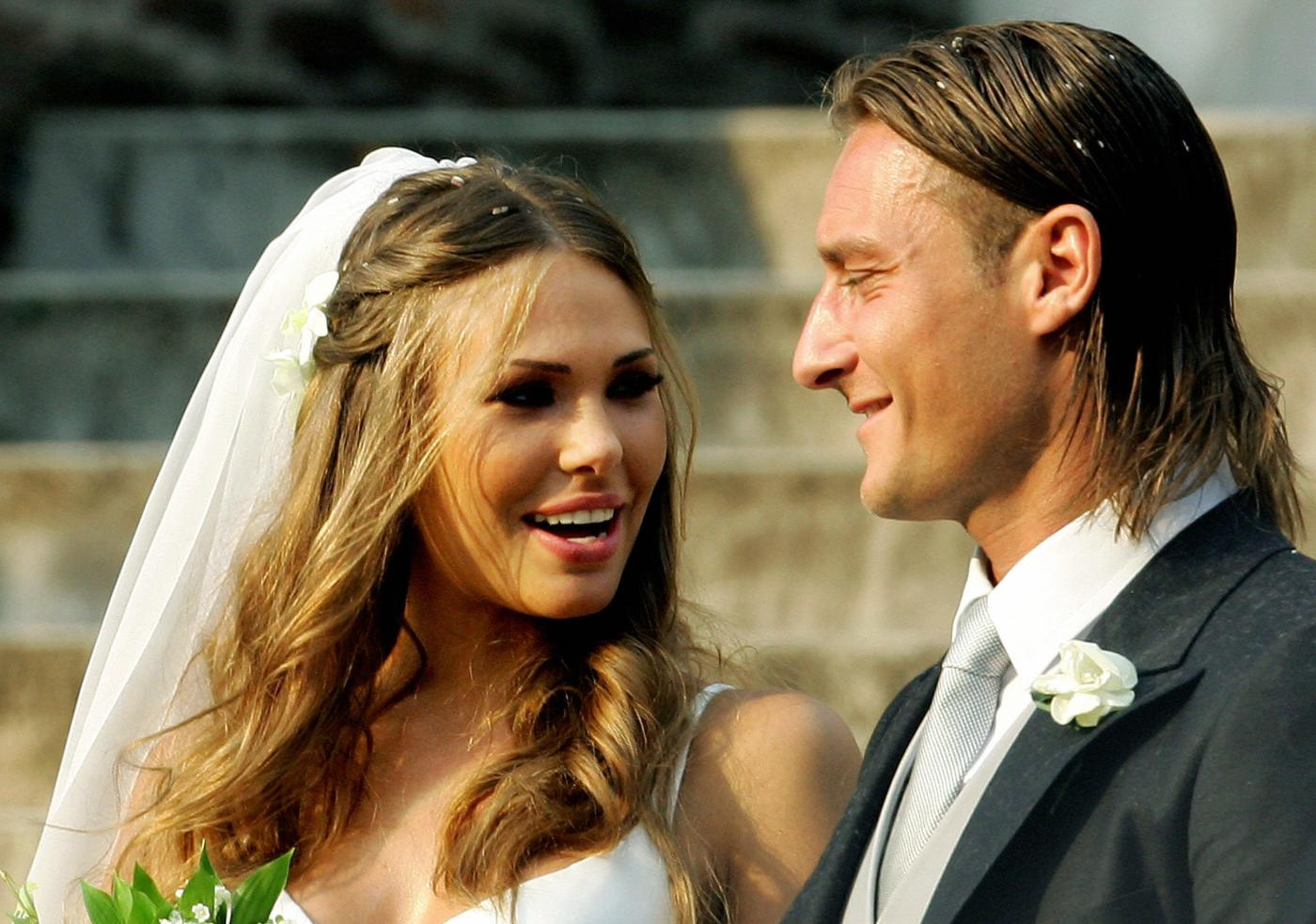 Rome, ITALY: AS Roma captain Francesco Totti (R) smiles to his wife Italian TV star Hilary Blasi leave the church after their wedding 19 June 2005 in Rome. AFP PHOTO/VINCENZO PINTO (Photo credit should read VINCENZO PINTO/AFP/Getty Images)