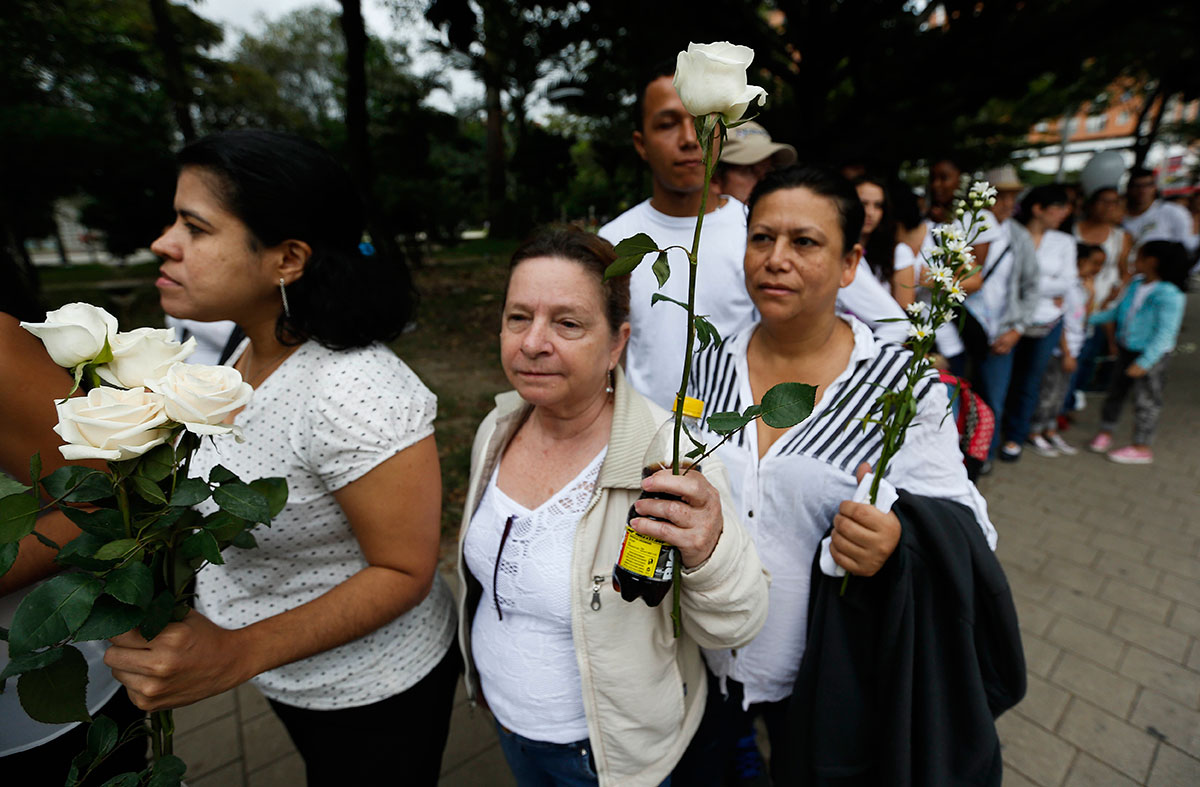 Fans of Colombia's Atletico Nacional football club arrive for a tribute to members of Brazil's Chapecoense team who died in a plane crash, at Atanasio Girardot stadium where they were to play a game in Medellin, Colombia. [Fernando Vergara/AP]