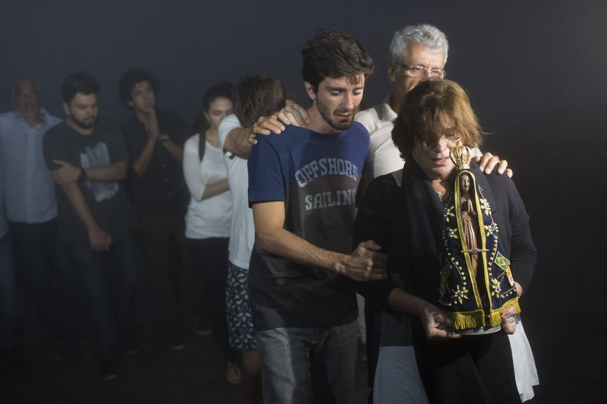 Holding a statue of Our Lady of Aparecida, Ana Maria is followed by her son Henrique Senges and husband Fernando Jose during a ceremony in memory of her late son, journalist Guilherme Marques who died in a plane crash, near the Christ the Redeemer statue in Rio de Janeiro, Brazil, Tuesday, Nov. 29, 2016. A chartered plane that was carrying the Brazilian football team Chapecoense to the biggest match of its history, as well as members of the press, crashed into a Colombian hillside and broke into pieces, killing most passengers, Colombian officials said Tuesday. (AP Photo/Leo Correa)