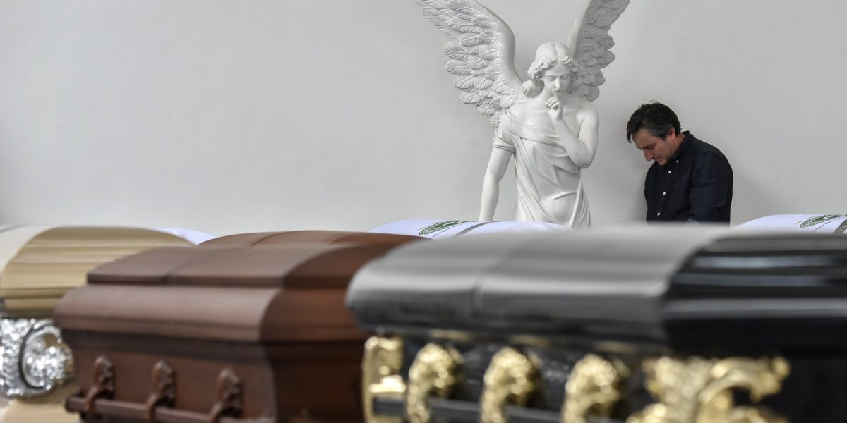Roberto D'Machi, a relative of Nilson Junior Folle, one of the players of Brazilian football team Chapecoense Real killed in a plane crash in the Colombian mountains, mourns next to his coffin at the San Vicente mortuary in Medellin on December 1, 2016. The pilot of a charter plane carrying the Brazilian football team Chapecoense Real radioed frantically that he was out of fuel minutes before slamming into a hillside near Medellin with 77 people on board, an audio recording showed. / AFP / Luis ACOSTA (Photo credit should read LUIS ACOSTA/AFP/Getty Images)