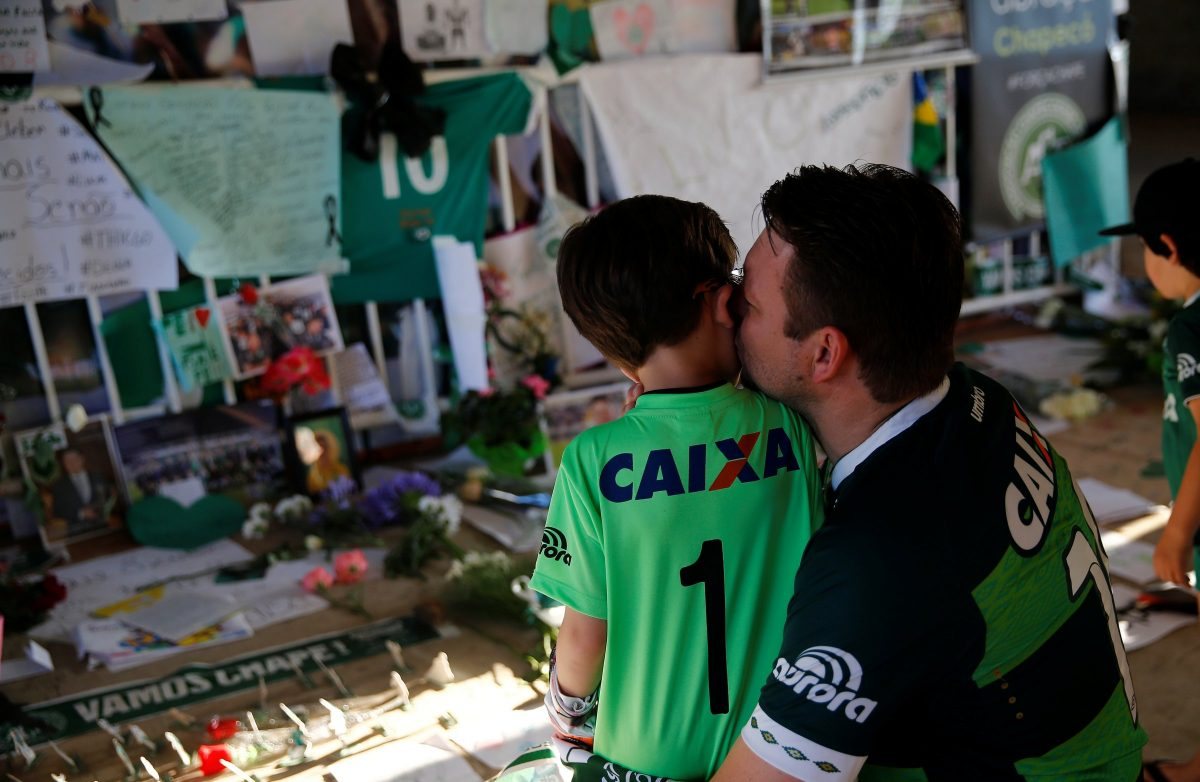 A man kisses his child during a tribute to Chapecoense players at the Arena Conda stadium in Chapeco, Brazil December 1, 2016. [Ricardo Moraes/Reuters ]