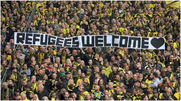 Borussia Dortmund fans in support to welcome refugees (source: www.theguardian.com)