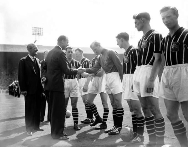 Manchester City keeper Bert Trautmann bows his head as he is introduced to HRH, The Duke of Edinburgh (Prince Phillip) before the 1956 FA Cup Final (Source: www.whoateallthepies.tv)