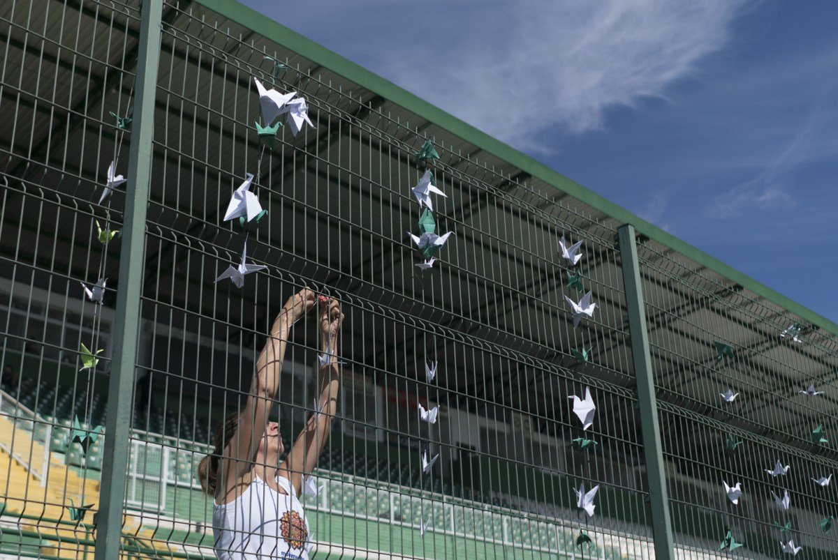 A volunteer hangs paper cranes on the gates of the stadium Arena Conda, home of the Chapecoense Brazilian football team, in Chapeco, Brazil, Friday, Dec. 2, 2016. Members of the team and a group of journalists perished on a chartered flight earlier in the week. They were headed to the Copa Sudamericana finals when the chartered plane they were travelling in ran out of fuel, crashing into the Andes outside Medellin. Renata Brito AP Photo