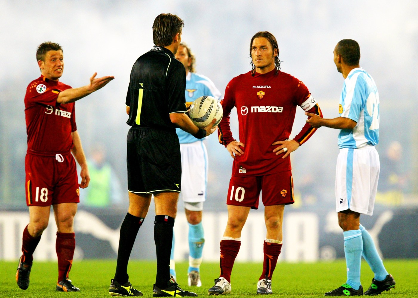 "AS Roma's Antonio Cassano (L) and Francesco Totti (2R) talk with the referee Roberto Rosetti (2L) and Lazio's players Sinisa Mihajlovic and Fabio Liverani (R) during the suspension of the Serie A match at the Olympic Stadium in Rome March 21, 2004. The ""derby"" match between Rome arch-rivals Lazio and AS Roma was abandoned on Sunday after false rumours circulated among fans that a child had been killed by a police car outside the stadium. REUTERS/Giampiero Sposito"