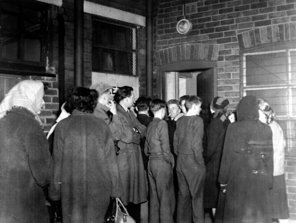 Supporters of Manchester United gather around the Old Trafford offices to hear news of the plane crash in Munich which killed 21.