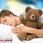 Young man lying asleep in bed with a teddy bear - ibxaib03082788.jpg