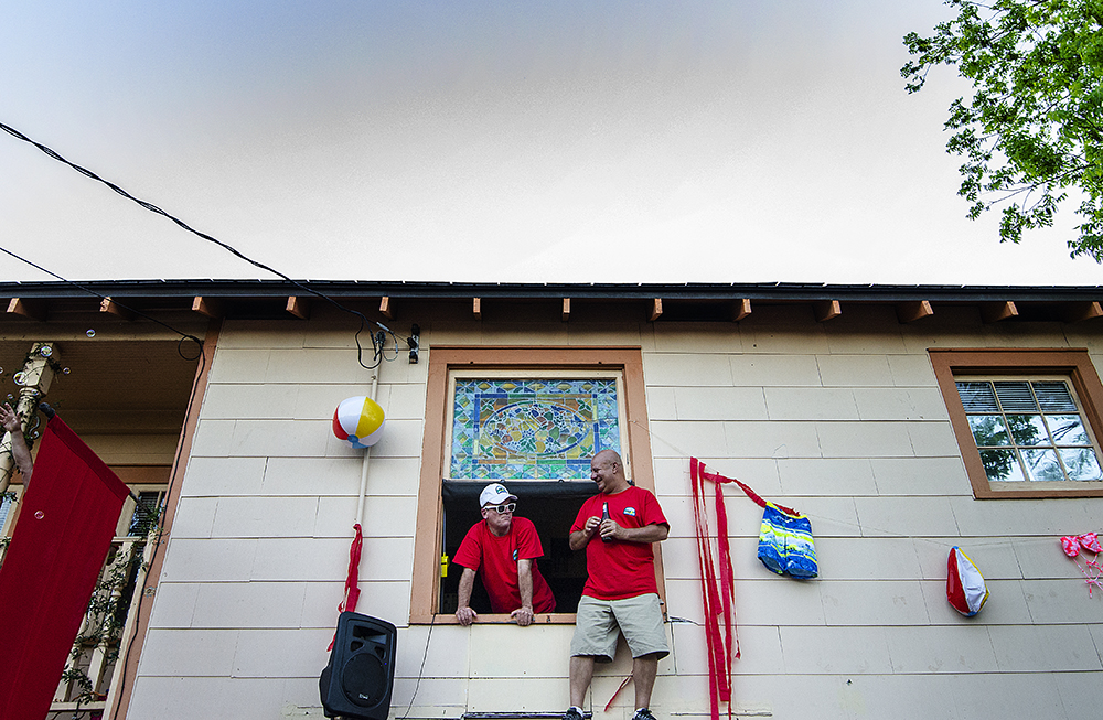 April 22, 2016 - New Orleans, LA: Two men watch from above while the street party begins to form at The Bubble House, the first residence festival goers pass when exiting the New Orleans Jazz and Heritage Festival onto Mystery Street. The Bubble House is exactly what it sounds like, a house full of partiers that emits a constant stream of bubbles, each year with a different theme. This year's theme is Summer Camp. (Photo by Katie Sikora)
