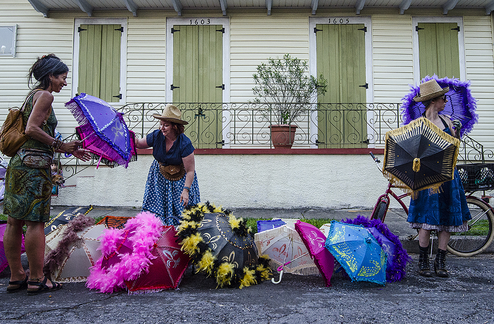 April 22, 2016 - New Orleans, LA: Attendants of the New Orleans Jazz and Heritage Festival spill out of every exit into growing street parties on each of the nearest streets following the fest. Many local artists and characters set up shop during these after parties, including these two women who sold custom secondline umbrellas, some including The Love Symbol honoring the late Prince Rogers Nelson. (Photo by Katie Sikora)