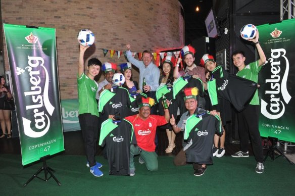 Seven guests posing for winning personalised jerseys from Carlsberg's juggling football challenge at the launch event of Play on Pitch campaign
