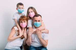 young family in medical masks during home quarantine