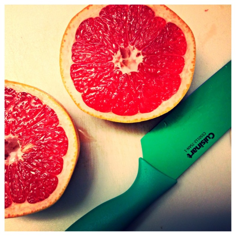 Grapefruit with green knife.