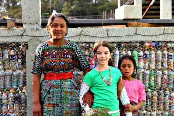 Hug it Forward school children in front of the bottle wall