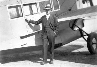 Harry Smith next to the cabin door of a Loening