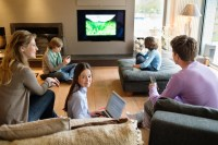 Family using electronic gadgets in a living room | Grewal ...