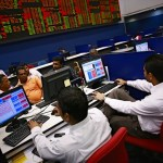 Investors and brokers monitor the market at the Colombo Stock Exchange