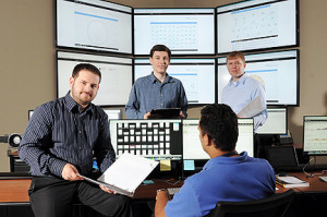 Georgia Tech Research Institute (GTRI) cyber-security specialists Christopher Smoak, Bryan Massey and Ryan Spanier (l-r) pose in facilities used to gather information on the activities of hackers and pending cyber attacks. GTRI has developed a new open source intelligence gathering system known as BlackForest. (Credit: Gary Meek)