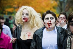 A couple dressed as zombies - Danny Zucco and Sandy Olsson from the movie Grease walking in the annual Toronto Zombie Walk.