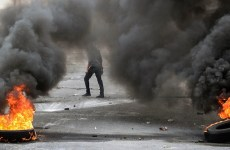 Protester walks behind two sets of burnt tires  in the