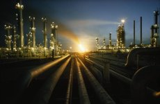 Gas fires light the sky as a heavily lit oil refinery glows at night