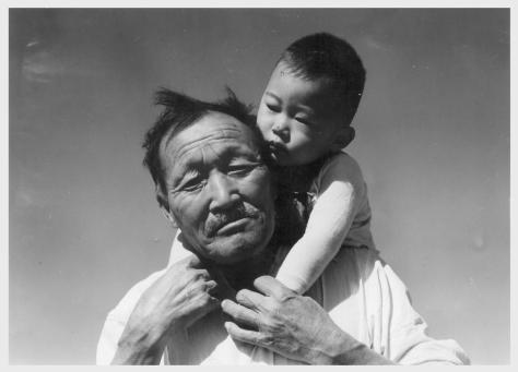 Dorothea Lange. Manzanar, California. 7/2/42. Grandfather and grandson of Japanese ancestry at this War Relocation Authority center.